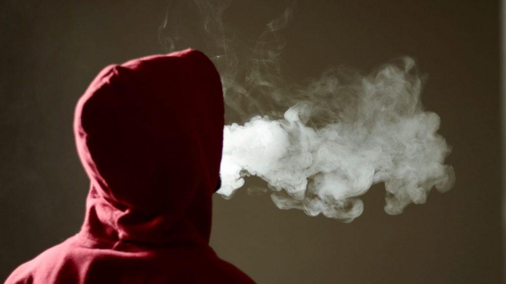 teenager in red hoodie smoking vape