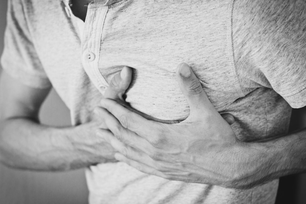 A black and white image of a man clutching his chest in pain.