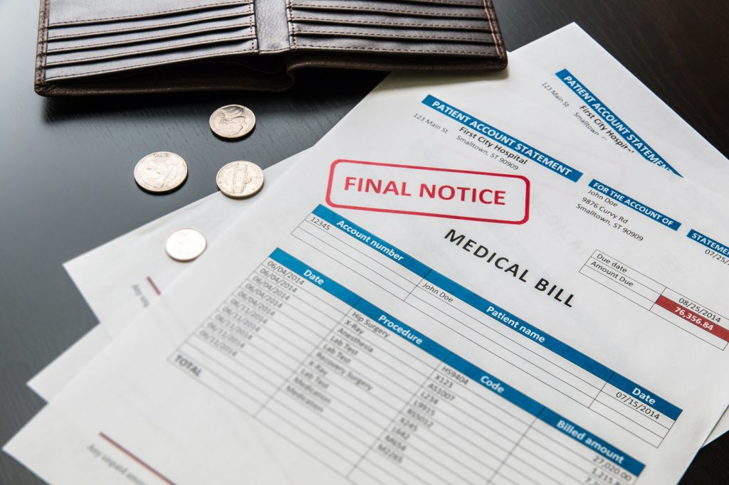 """Medical bills with the stamp """"final notice"""" on them. Next to a wallet with no money left in it."""