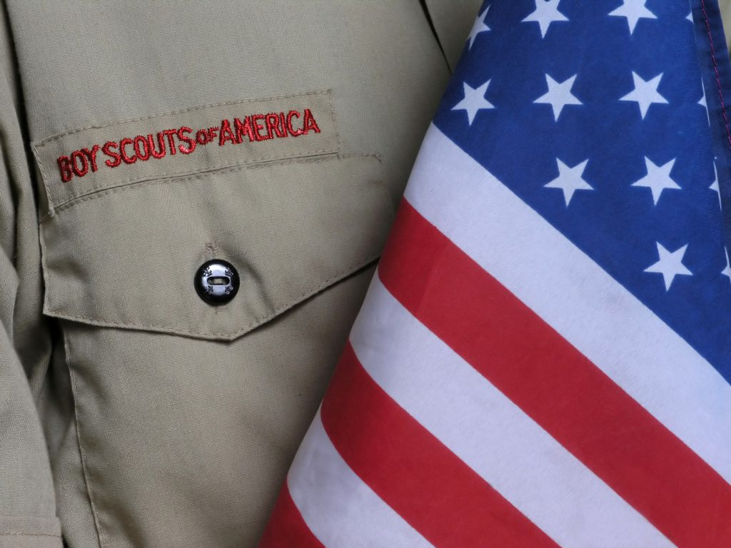 A closeup of a Boy Scouts of America uniform next to the US flag.