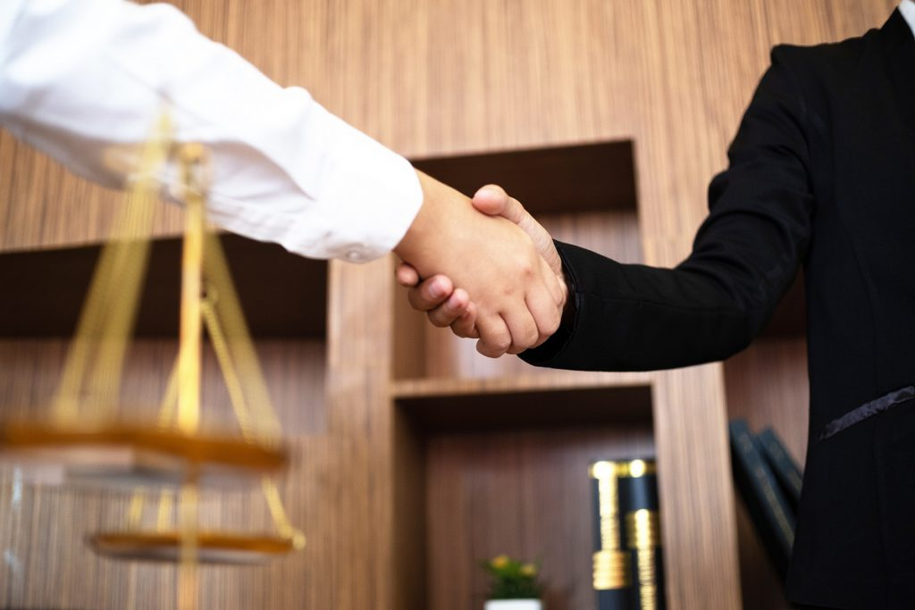 An attorney shaking hand with a client.