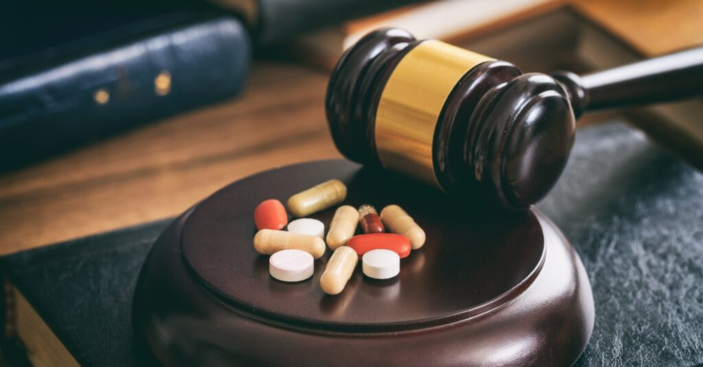 A judge's gavel next to a pile of pills.