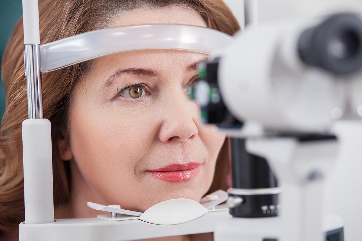 A woman receiving an eye exam from an eye examination machine