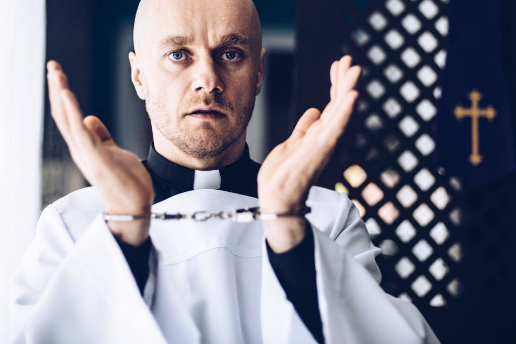 Catholic priest in handcuffs in church.