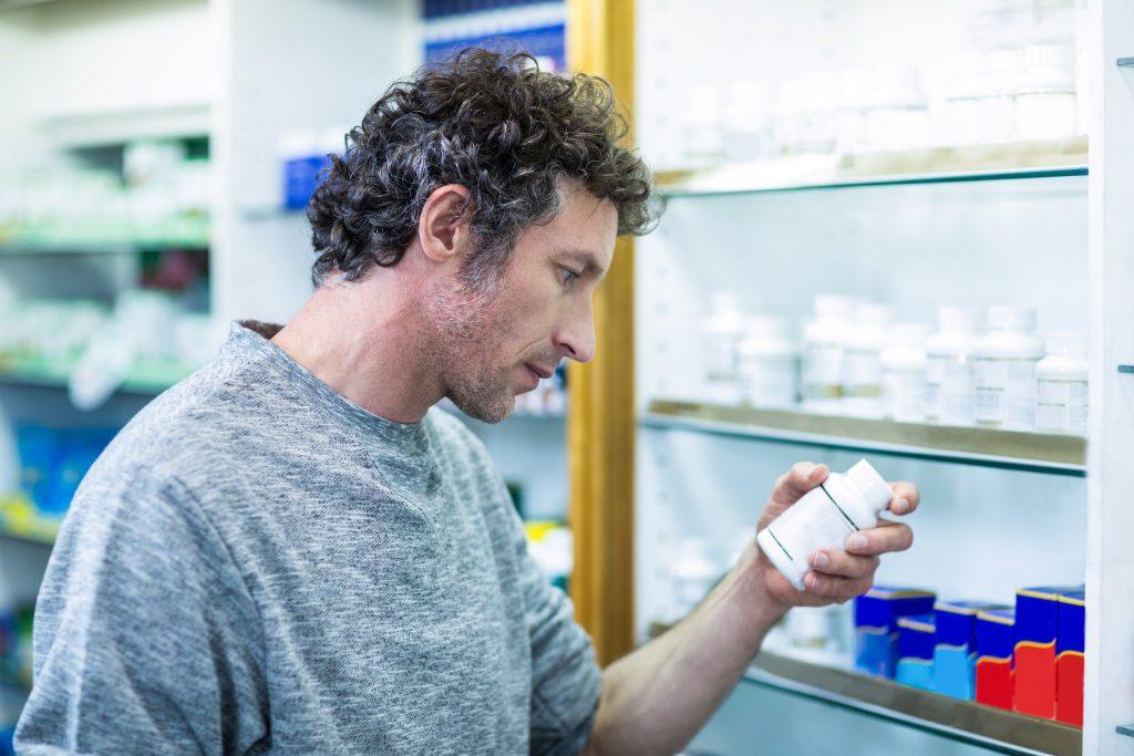 Customer holding a pill box in pharmacy