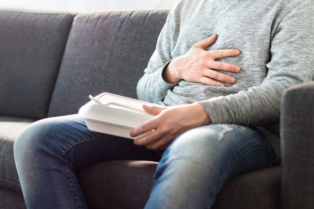 Man ate too much and is holding belly with hand