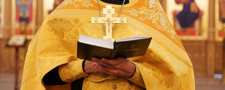 Priest hands holding holy bible book in church
