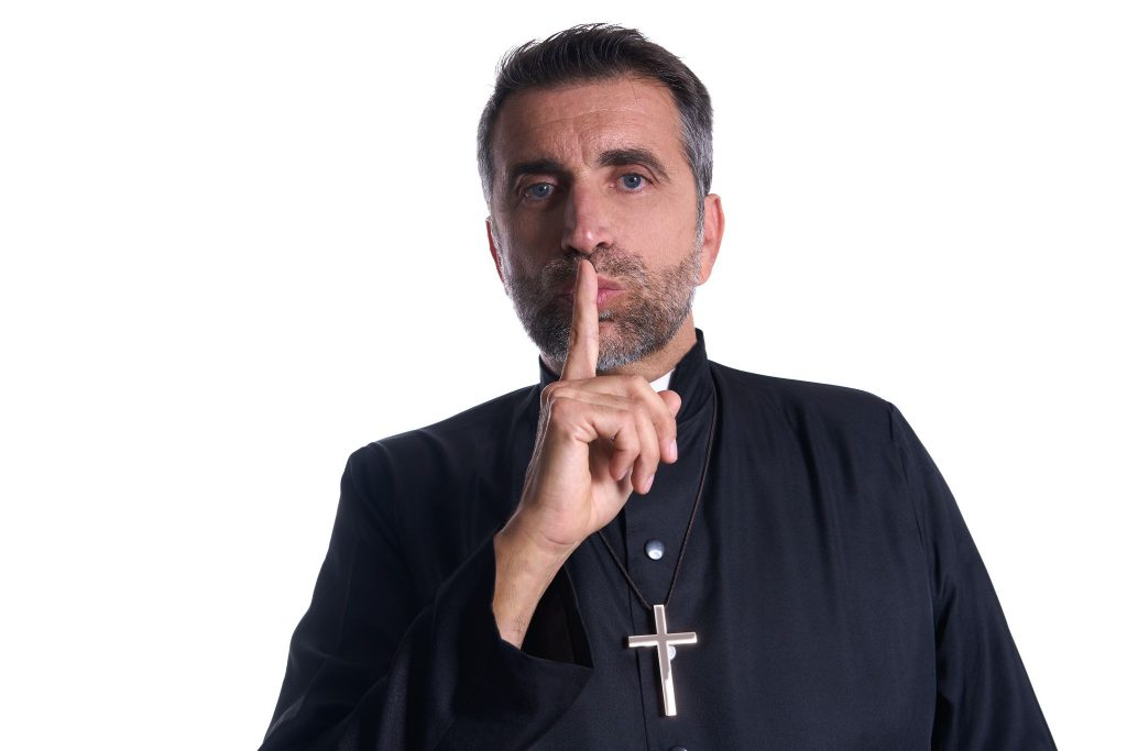 Priest with finger in lips as a silence expression request