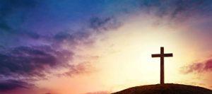Silhouette cross on Calvary mountain sunset