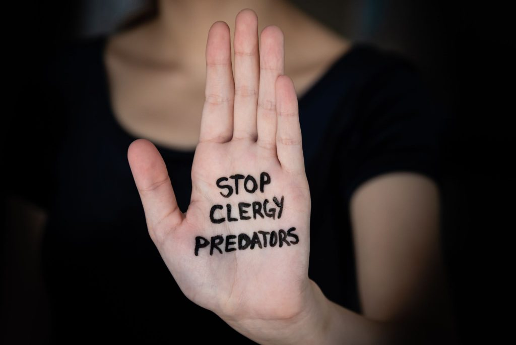 Woman holding hand into the light with words Stop Clergy Predators