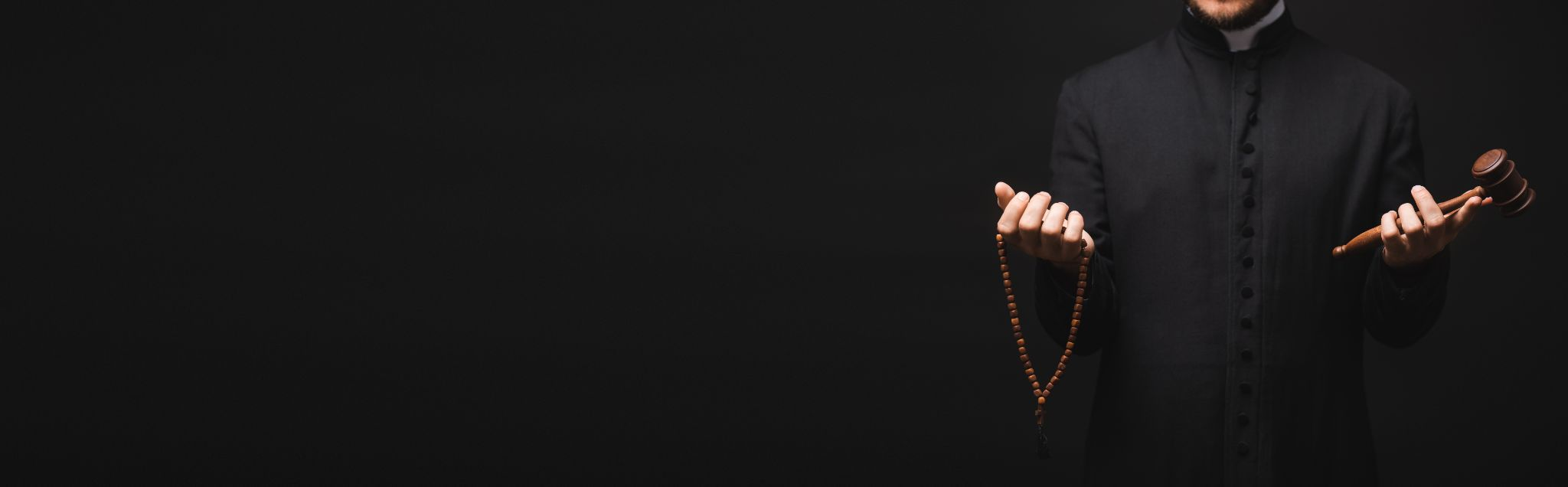 priest holding wooden gavel and rosary beads in hands