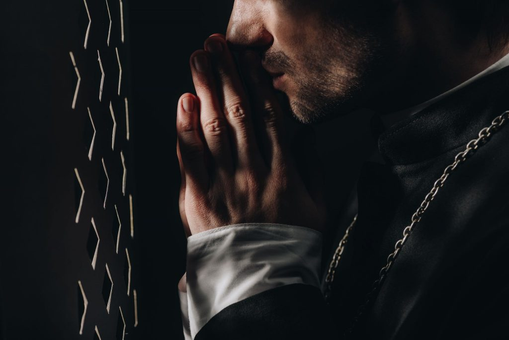 young catholic priest praying with closed eyes near confessional grille